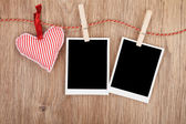 Blank instant photos and red heart hanging on the clothesline — Stock Photo