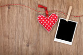 Blank instant photo and red heart hanging on the clothesline — Stock Photo