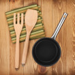 Stock Photo: Frying pan and kitchen utensils on wooden table