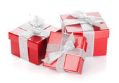 Three red gift boxes with silver ribbon and bow — Stockfoto