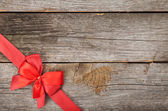 Wooden background with red bow and ribbon — Foto de Stock