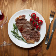 Sirloin steak with rosemary and cherry tomatoes on plate — Stock Photo #40075585