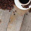 Coffee cup and beans on wooden table — Stock Photo