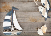 Toy sailboat and fish with seashells on a wooden background — Stok fotoğraf