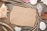 Old paper with rope and seashells on wooden textured background — Stock Photo