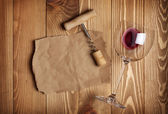 Red wine glass, corkscrew and paper for your note — Stock Photo