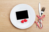 Valentine's Day blank photo frame over plate and silverware — Stock Photo