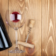 Red wine bottle glass and corkscrew — Stock Photo