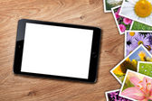 Tablet with blank screen and stack of printed pictures collage — Stock Photo