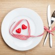 Valentine's Day heart shaped red ribbon over plate with silverware — Stock Photo #42043319