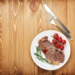 Sirloin steak with rosemary and cherry tomatoes on a plate — Stock Photo #42043469