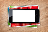 Phone with blank screen over stack of printed pictures collage — Stockfoto