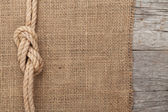 Ship rope on wood and burlap texture background — Stock Photo