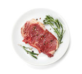 Raw sirloin steak with rosemary and spices on plate — Stock Photo