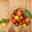 Colorful cherry tomatoes on wooden table — Stock Photo #42278741