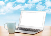 Laptop with blank screen and cup on table — Stock Photo