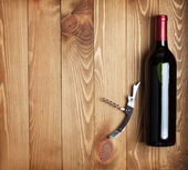Red wine bottle and corkscrew — Stock Photo