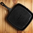 Frying pan on wooden table background — Stock Photo
