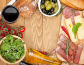 Red wine with cheese, olives, tomatoes, prosciutto, bread and spices — Stock Photo