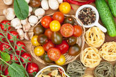 Fresh ingredients for cooking: pasta, tomato, cucumber, mushroom — ストック写真