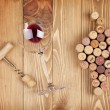 Red wine glass, corkscrew and corks — Stock Photo