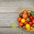 Colorful cherry tomatoes on wooden table — Stock Photo #43167925