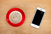 Mobile phone and coffee cup — Stok fotoğraf