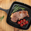 Sirloin steak with rosemary and cherry tomatoes on frying pan — Stock Photo