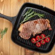 Sirloin steak with rosemary and cherry tomatoes on frying pan — Stock Photo #43979627