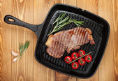 Sirloin steak with rosemary and cherry tomatoes on frying pan — Stok fotoğraf