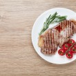 Sirloin steak with rosemary and cherry tomatoes on a plate — Stock Photo #43980015