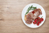 Sirloin steak with rosemary and cherry tomatoes on a plate — Stock Photo