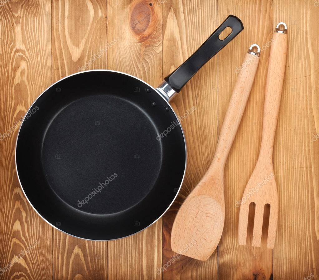 Frying pan and kitchen utensils on wooden table stock for Table utensils