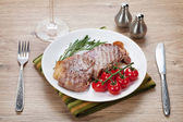 Sirloin steak with rosemary and cherry tomatoes on a plate — Zdjęcie stockowe