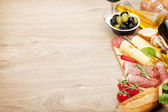 Red wine with cheese, prosciutto, bread, vegetables and spices — Stock Photo