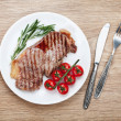 Sirloin steak with rosemary and cherry tomatoes on a plate — Stock Photo #46238923