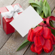Fresh red tulips with gift box and greeting card — Stock Photo
