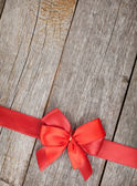 Wooden background with red bow and ribbon — Stock Photo