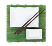 Chopsticks and utensils over bamboo mat — Stock fotografie