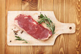 Raw sirloin steak with rosemary and spices on cutting board — Stok fotoğraf