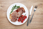 Sirloin steak with rosemary and cherry tomatoes on a plate — Stock fotografie