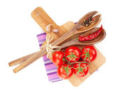 Tomatoes with spices and kitchen utensils — Stock Photo