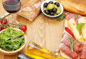 Red wine with cheese, prosciutto, bread, vegetables — Stock Photo