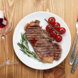 Sirloin steak with rosemary and cherry tomatoes on a plate — Stock Photo #47762467