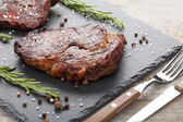 Beef steaks with rosemary and spices — Stock Photo
