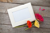Gerbera flowers and photo frame — Stock Photo