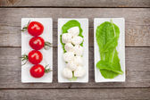 Tomatoes, mozzarella and salad leaves — ストック写真
