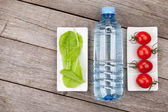 Green salad leaves, water bottle and tomatoes — Stock Photo