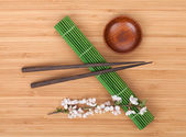 Chopsticks and sakura branch — Stock Photo