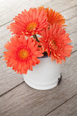 Orange gerbera flowers in pitcher — Stock Photo